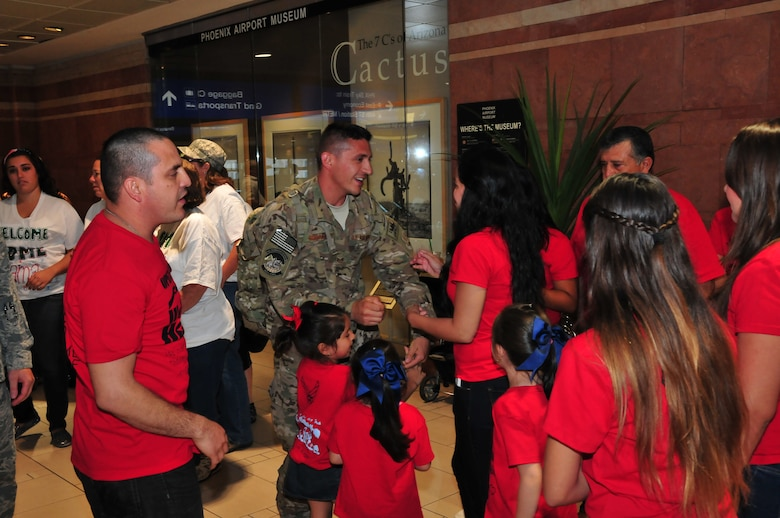 Staff Sgt. Jesus Rosales of the 161st Air Refueling Wing Logistics Readiness Squadron is welcomed back to Arizona by his friends and family at the Phoenix Sky Harbor International Airport after his recent deployment, Oct. 3, 2014. Fourteen Airmen from the 161st ARW Aerial Port spent seven months in Afghanistan in support of Operation Enduring Freedom. (U. S. Air National Guard photo by Master Sgt. Kelly M. Deitloff/released)