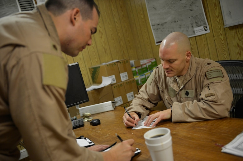(Right) U.S. Air Force Maj. Vincent Sherer, 455th Ai r Expeditionary Wing, A-10 Thunderbolt II pilot, reviews checklists before a sortie at Bagram Airfield, Afghanistan Aug. 5, 2014.  Sherer has been flying for 12 years and has deployed to Bagram four times.  He is deployed from Davis-Monthan Air Force Base, Ariz. and a native of Portland, Ore. (U.S. Air Force photo by Staff Sgt. Evelyn Chavez/Released)