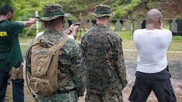 Staff Sgt. Milton Donatus, center left, and Lance Cpl. Dale A. Lane, center right, supervise Palau national law enforcement officers during live-fire training with the M9A1 9 mm service pistol Sept. 16 in Irai, Palau. The training gave the Palauan police officers a chance to learn Marine Corps marksmanship fundamentals and familiarized them with the weapon. The training is part of exercise T-AKE 14-2, a maritime pre-positioned force, multi-country theater security cooperation event that deploys from Okinawa aboard the USNS Sacagawea to conduct training exercises. Donatus is from Ngaraard, Palau, and is the training chief with Combat Logistics Detachment 379, Combat Logistics Regiment 37, 3rd Marine Logistics Group, III Marine Expeditionary Force. Lane is from Newton Falls, Ohio, and is a military policeman with the detachment.