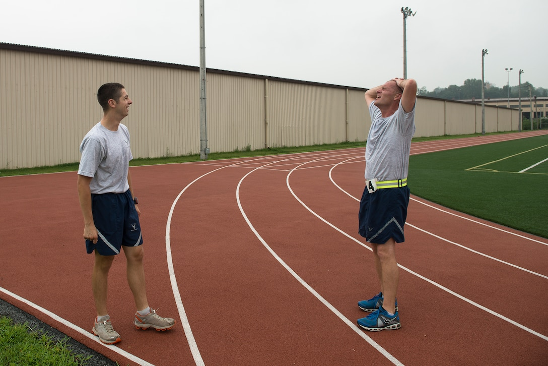 Staff Sgt. Joshua Johnson, a 51st Operations Support Squadron airfield management operations supervisor, cools down with a coworker after running with him for a PT test Aug. 7, 2014, at Osan Air Base, Republic of Korea. Johnson does a variety of fitness-related activity within his squadron, including leading PT sessions and off-duty running. (U.S. Air Force photo by Staff Sgt. Jake Barreiro/Released)