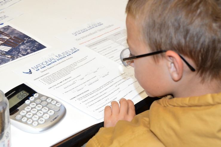 Picture of a boy working on a paper with a calculator