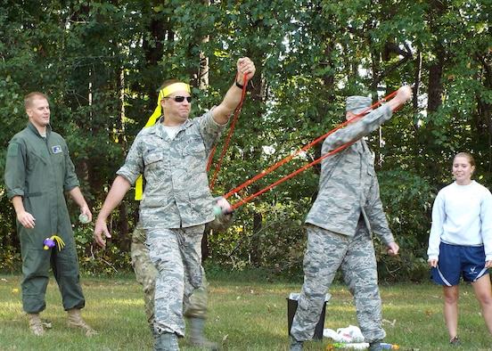 Members of the 80th Aerial Port Squadron participate in a water balloon toss at their unit combat dining in Oct. 4, 2014, at Dobbins Air Reserve Base, Ga. The celebration allows Airmen of all ranks to come together and celebrate unit and individual accomplishments. (U.S. Air Force photo by Staff Sgt. Karla Lehman/Released)