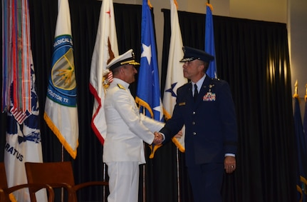 Rear Adm. William Roberts congratulates Brig. Gen. Robert Miller on relieving him as the new Medical Education and Training Campus commandant during a Change of Commandant ceremony September 24. Miller is METC's first Air Force commandant, a position that also inherits the dual hat of Education & Training (E&T) director for  the new Defense Health Agency.  Lt. Gen. Douglas Robb, Director of the Defense Health Agency, presided over the ceremony while the Honorable Dr. Jonathan Woodson, Assistant Secretary of Defense for Health Affairs, served as guest speaker  (Photo by Lisa Braun)