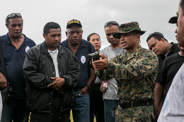 Marine Corps Staff Sgt. Milton Donatus, second from right, instructs Palau national law enforcement officers on the operations of the M9A1 9 mm service pistol in Irai, Palau, Sept. 16, 2014. Donatus is a native of Ngaraard, Palau. U.S. Marine Corps photo by Lance Cpl. Drew Tech