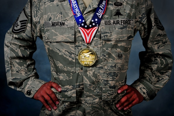U.S. Air Force Master Sgt. Juanjose Moran, 26th Special Tactics Squadron flight chief, 24th Special Operations Wing, dons his AF Marathon medal.  Moran recently crossed the 2014 Air Force Marathon's 26.2 mile finish line in 2:37 as the first active duty military winner and third overall finisher. (U.S. Air Force photo/Staff Sgt. Matthew Plew)