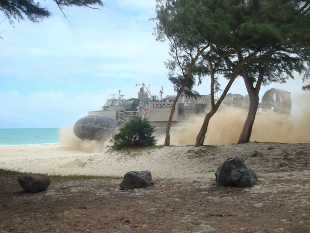 An LCAC with vehicles from Battery R lands on the beach at MCTAB, Oahu, Hawaii on 14 July 2014.