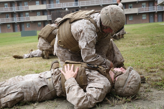 Marines with the Ground Combat Element Integrated Task Force apply simulated care under fire as part of an evaluation during combat lifesaver course at the task force barracks, at Marine Corps Base Camp Lejeune, North Carolina Oct. 3, 2014. Marines simulated carrying a casualty to a safe area and applying first aid. From October 2014 to July 2015, the GCEITF will conduct individual and collective level skills training in designated ground combat arms occupational specialties in order to facilitate the standards based assessment of the physical performance of Marines in a simulated operating environment performing specific ground combat arms tasks. (U.S. Marine Corps photo by Cpl. Paul S. Martinez/Released)