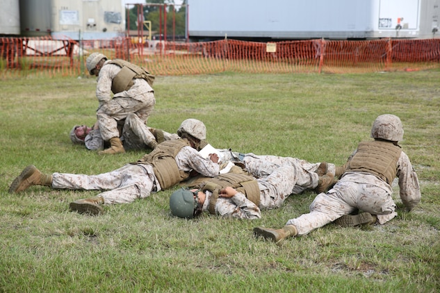 Marines with the Ground Combat Element Integrated Task Force react to a simulated ambush as part of an evaluation during combat lifesaver course at the task force courtyard at Marine Corps Base Camp Lejeune, North Carolina, Oct. 3, 2014. Marines simulated carrying a casualty to a safe area and applying first aid. From October 2014 to July 2015, the GCEITF will conduct individual and collective level skills training in designated ground combat arms occupational specialties in order to facilitate the standards based assessment of the physical performance of Marines in a simulated operating environment performing specific ground combat arms tasks. (U.S. Marine Corps photo by Cpl. Paul S. Martinez/Released)