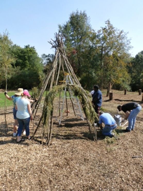 Willow artist and volunteers create structure for Playscape area
