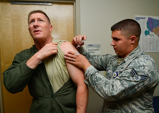 Col. Michael Grismer, 436th Airlift Wing commander, receives his annual influenza shot from Senior Airman Jeffrey Utz, 436th Medical Operations Squadron allergy and immunizations technician, Aug. 6, 2014, at the 436th Immunizations Clinic on Dover Air Force Base, Del. The clinic administered more than 6,000 flu vaccines to active duty, retirees and dependents. (U.S. Air Force photo/Airman 1st Class William Johnson)