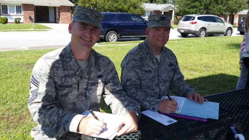Colonel Jeffrey DeVore, Joint Base Charleston commander, and Chief Master Sgt. Mark Bronson, 628th Air Base Wing command chief, fill out their Forest City Resident Satisfaction Surveys Oct. 1, 2014, at Hunley Park on Joint Base Charleston, S.C. The Resident Satisfaction Survey allows Forest City residents an opportunity to provide feedback to Forest City management. Forest City residents will be able to fill out the survey throughout the month of October. (Courtesy photo)