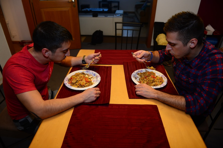 U.S. Air Force Senior Airman Edward Lomelin, 606th Air Control Squadron radio frequencies transmission systems technician and native of Austin, Texas, and U.S. Air Force Airman 1st Class Chris Lomelin, 606th ACS power production technician and native of Austin, Texas, eat dinner together at their home in Bitburg, Germany, Oct. 1, 2014. Edward, Chris' older brother, helped to prepare Chris for his first deployment to Southwest Asia. This will be Edward's fourth deployment. (U.S. Air Force photo by Airman 1st Class Kyle Gese/Released)