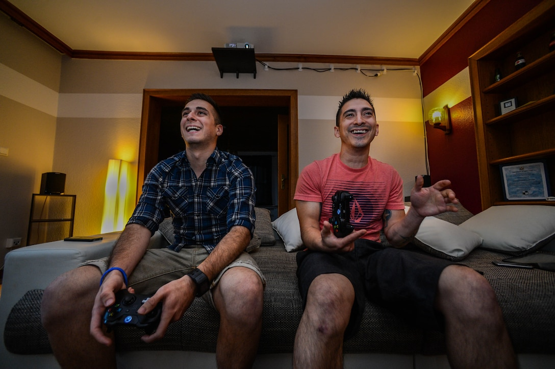 U.S. Air Force Senior Airman Edward Lomelin, 606th Air Control Squadron radio frequencies transmission systems technician and native of Austin, Texas, and U.S. Air Force Airman 1st Class Chris Lomelin, 606th ACS power production technician and native of Austin, Texas, play video games together at their home in Bitburg, Germany, Sept. 27, 2014. The 606 ACS is a self-contained mobile combat unit with Airmen covering more than 21 specialties maintaining over $170 million worth of equipment. The squadron routinely trains to prepare for deployments. The Lomelins deployed together to support Operation Enduring Freedom. (U.S. Air Force photo by Airman 1st Class Kyle Gese/Released)