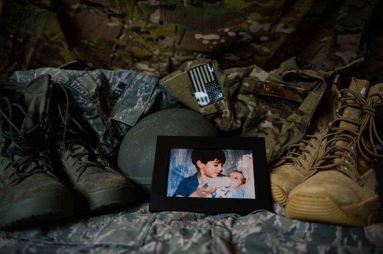 A photograph of U.S. Air Force Senior Airman Edward Lomelin, 606th Air Control Squadron radio frequencies transmission systems technician and native of Austin, Texas, feeding his younger brother U.S. Air Force Airman 1st Class Chris Lomelin, 606th ACS power production technician and native of Austin, Texas, rests on their uniforms at their home in Bitburg, Germany, Sept. 26, 2014. Edward and Chris recently prepared themselves to deploy to Southwest Asia in support of Operation Enduring Freedom. Both brothers are stationed together at Spangdahlem Air Base, Germany, and operate out of the same squadron. (U.S. Air Force photo by Airman 1st Class Kyle Gese/Released)