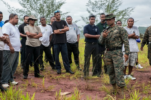 """Staff Sgt. Milton Donatus, right, instructs Palau national law enforcement officers on the operations of the M9A1 9 mm service pistol Sept. 16 in Irai, Palau. The chance to come home and instruct the training was a very meaningful experience, according to Donatus, who is from Ngaraard, Palau. """"It feels good and it means a lot to me to come back in this situation,"""" said Donatus, the training chief with Combat Logistics Detachment 379, Combat Logistics Regiment 37, 3rd Marine Logistics Group, III Marine Expeditionary Force. """"I was not a wealthy kid growing up, so people kind of always looked at me thinking that I wouldn't amount to anything. Being able to come back with a different life is just awesome because it gives me a chance to show everyone who grew up where I did that there is hope."""" The training is part of exercise T-AKE 14-2, a maritime pre-positioned force, multi-country theater security cooperation event that deploys from Okinawa aboard the USNS Sacagawea to conduct training exercises. (U.S. Marine Corps photo by Lance Cpl. Drew Tech/Released)"""