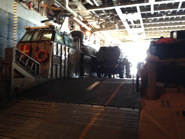 A M142 HIMARS launcher and a M1114 HMMWV from Battery R are loaded onto a Landing Craft Air Cushion (LCAC) in the well deck of the USS Peleiu (LHA-5).