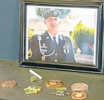 Coins adorn a memorial display during a ceremony for Staff Sgt. Joseph Cunningham Sept. 18 at Morris Hill Chapel.