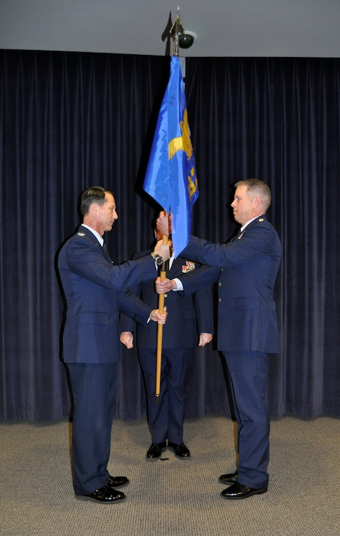 Col. Karl Stark (left), 152nd Airlift Wing Commander passes the flag to Lt. Col. Tony Machabee (right), the new 192nd Airlift Squadron Commander as he assumes responsibility as the newly appointed commander. (USAF Photo by Master Sgt. Paula Macomber, 152nd Airlift Wing Public Affairs/RELEASED.)