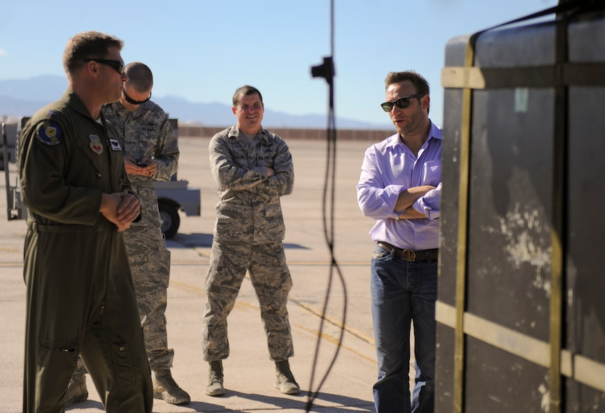 Simon Sinek, an internationally renowned speaker and author, is briefed by a member of the 66th Rescue Squadron during his visit to Nellis Air Force Base, Nev., Oct. 1, 2014. While visiting the 66th Rescue Squadron, Sinek was briefed about the capabilities and mission of the HH-60 Pave Hawk helicopter. (U.S. Air Force photo by Airman 1st Class Mikaley Towle)