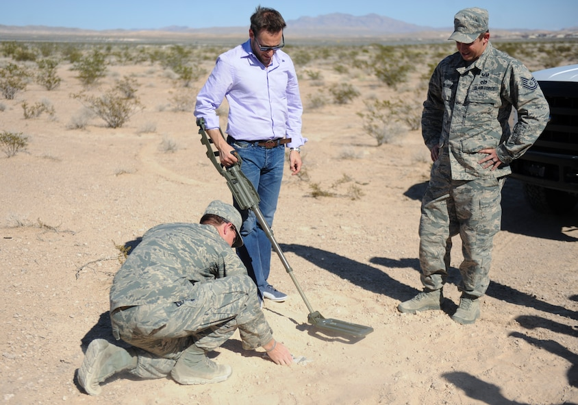 Simon Sinek, an internationally renowned speaker and author, uses a metal detector to locate a mine set up by Explosive Ordinance Disposal Airmen at Nellis Air Force Base, Nev., Oct. 1, 2014. Sinek's visit also included interactions with 99th Security Forces Squadron Military Working Dog handlers and 58th Rescue Squadron members, a visit to the 66th Rescue Squadron to look at the HH-60 Pave Hawk helicopter, and finished with a mission briefing at the Red Flag building. (U.S. Air Force photo by Airman 1st Class Mikaley Towle)