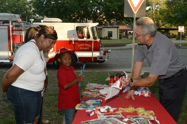 """Dan Flores, Joint Base San Antonio-Randolph Fire Emergency Services captain, hands out fire prevention education pamphlets to Carolyn Wellons and her son, Lemarion Burley, JBSA-Randolph Family Housing residents, during """"National Night Out"""" Oct. 7, 2014, at JBSA-Randolph. NNO is a nationwide effort to heighten crime prevention awareness, generate support for local anti-crime programs and strengthen neighborhood spirit and police-community partnerships for a safer nation. (U.S. Air Force photo by Johnny Saldivar)"""