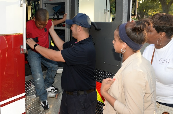 """Tim Hagan, Joint Base San Antonio-Randolph firefighter, helps Lemarion Burley after giving him a tour of the inside of fire engine 303 during """"National Night Out"""" Oct. 7, 2014, at Joint Base San Antonio-Randolph. NNO is a nationwide effort to heighten crime prevention awareness, generate support for local anti-crime programs and strengthen neighborhood spirit and police-community partnerships for a safer nation. (U.S. Air Force photo by Johnny Saldivar)"""