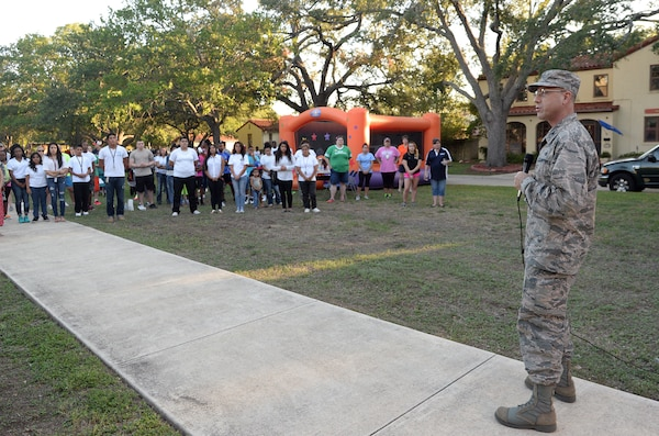 """Col. Michael Gimbrone, 502nd Security Forces and Logistics Support Group commander, addresses the crowd during """"National Night Out"""" Oct. 7, 2014, at Joint Base San Antonio-Randolph. NNO is a nationwide effort to heighten crime prevention awareness, generate support for local anti-crime programs and strengthen neighborhood spirit and police-community partnerships for a safer nation. (U.S. Air Force photo by Johnny Saldivar)"""