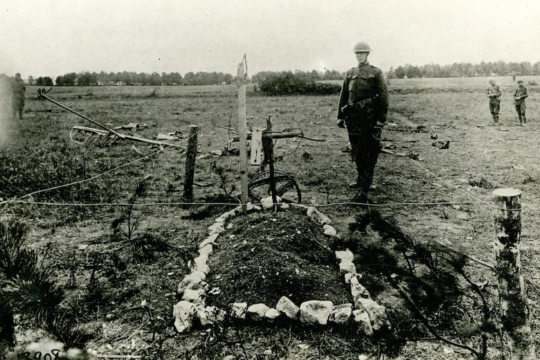 A U.S. soldier standing by Roosevelt's grave, marked by the cross made by the Germans of Basswood saplings.  Pieces of the crashed Nieuport lay scattered around. (U.S. Air Force photo)