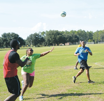 Petty Officer 1st Class Kewauna Stalls (center) attempts to deflect a pass, from an opposing team member, to Lt. Cmdr. Donald Mitchell during a handball game against fellow shipmates at Marine Corps Logistics Base Albany's Boyett Park, recently.