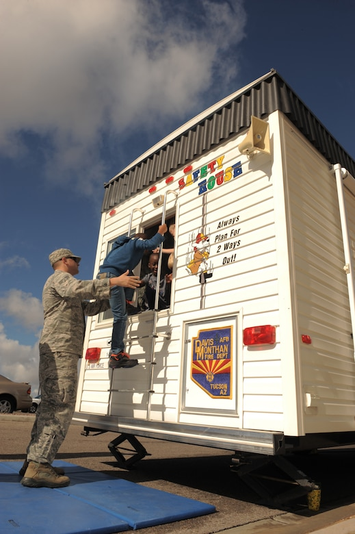 U.S. Air Force Senior Airman Christopher Ladue, 355th Fire Emergency Services firefighter, helps children from the School Age Program out of the window of a fire education trailer at Davis-Monthan Air Force Base, Ariz., Oct. 9, 2014. The fire education trailer is a simulated household environment intended to teach children how to identify fire hazards as well as how to safely evacuate a house in the event of a fire. (U.S. Air Force photo by Airman 1st Class Chris Drzazgowski/Released)
