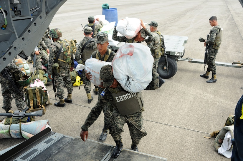 Honduran service members load bags of supplies onto a U.S. Army CH-47F Chinook October 8 during Operation Caravana.  Operation Caravana's sole purpose is to provide the Honduran military freedom of movement and access to the isolated areas in Gracias a Dios, Colon and Olancho in order to continue their security operations.  These troop movements and logistics re-supply flights will occur on an as-needed basis.  (Photo by U.S. Air National Guard Capt. Steven Stubbs)