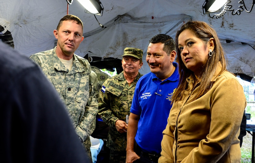 U.S. Army Lt. Col. Michael Alvis, deputy commander of the Medical Element; Rene Melgar, governor of La Paz; and Yanitza Rodriguez, representative from the La Paz Ministry of Human Rights are shown the mobile dental clinic as part of the Medical Readiness and Training Exercise site tour in San Marco, La Paz, Honduras, Oct. 8, 2014. The MEDRETE provided the citizens of San Marco an opportunity to receive basic medical care as well as providing the military members with the opportunity to train in a remote location. (U.S. Air Force photo by Tech. Sgt. Heather Redman/Released)