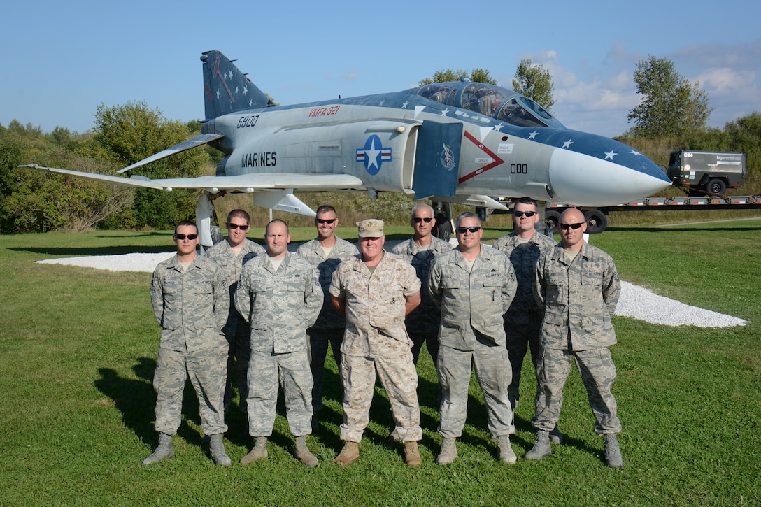 Truax-Longmire Veterans of Foreign Wars Post 8483 commander, and retired Marine Chief Warrant Officer Mike Wenger, center of front row, poses with the Wisconsin Air National Guard's 115th Fighter Wing Crash Damage or Disabled Aircraft Recovery team, following the installation of an F-4S Phantom static display on the post's grounds just north of Madison, Wis., Sept. 20, 2014. The eight airmen representing the 115 FW CDDAR team were able to complete critical training requirements by removing and relocating the aircraft to Madison from its previous home at Camp Atterbury, Ind. (Air National Guard Photo by Master Sgt. Paul Gorman)
