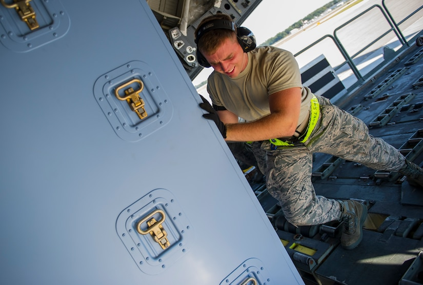 Airman 1st Class Luke Saylors, 437th Aerial Port Squadron air transportation technician, pushes cargo onto a C-17 Globemaster III, Oct. 8, 2014, on the flightline at Joint Base Charleston, S.C. In addition to their normal duties of loading and unloading C-17s, the 437th APS provides support for the nation's premier rapid deployment forces: XVIII Airborne Corps, 82nd Airborne Division, Joint Special Operations Command and the 43rd Airlift Wing. The squadron is prepared to meet short-notice, worldwide mobility taskings in support of national objectives, and plans and executes support for more than 50 percent of all joint airborne and air transportability training missions flown by Air Mobility Command and Reserve forces in support of Joint Operations. (U.S. Air Force photo/Airman 1st Class Clayton Cupit)