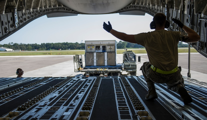 Airman 1st Class Luke Saylors, 437th Aerial Port Squadron air transportation technician, marshals in a 437th Atlas K-Loader towards a C-17 Globemaster III, Oct. 8, 2014, on the flightline at Joint Base Charleston, S.C. In addition to their normal duties of loading and unloading our C-17s, the 437th APS provides support for the nation's premier rapid deployment forces: XVIII Airborne Corps, 82nd Airborne Division, Joint Special Operations Command and the 43rd Airlift Wing. The squadron is prepared to meet short-notice, worldwide mobility taskings in support of national objectives, and plans and executes support for more than 50 percent of all joint airborne and air transportability training missions flown by Air Mobility Command and Reserve forces in support of Joint Operations. (U.S. Air Force photo/Airman 1st Class Clayton Cupit)