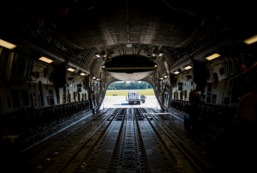 A 437th Aerial Port Squadron Atlas K-Loader sits behind a C-17 Globemaster III, Oct. 8, 2014, on the flightline at Joint Base Charleston, S.C. In addition to their normal duties of loading and unloading our C-17s, the 437th APS provides support for the nation's premier rapid deployment forces: XVIII Airborne Corps, 82nd Airborne Division, Joint Special Operations Command and the 43rd Airlift Wing. The squadron is prepared to meet short-notice, worldwide mobility taskings in support of national objectives, and plans and executes support for more than 50 percent of all joint airborne and air transportability training missions flown by Air Mobility Command and Reserve forces in support of Joint Operations. (U.S. Air Force photo/Airman 1st Class Clayton Cupit)