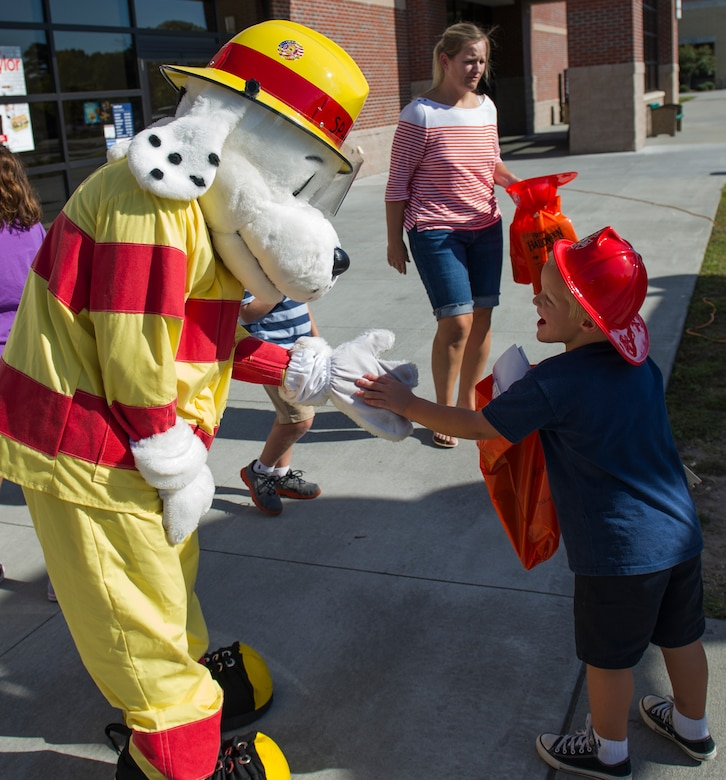 Sparky the fire dog greets children during a Joint Base Charleston Fire Department fire prevention week event Oct. 7, 2014, at the Air Base Exchange on JB Charleston, S.C. Fire prevention Week was Oct. 5 through 11, and the JB Charleston Fire Department hosted several events around the Air Base and Weapons Station. Fire prevention week was established in 1925 by President Calvin Coolidge when he became aware that close to 15,000 American citizens had been killed in fires the previous year. (U.S. Air Force photo/Airman 1st Class Clayton Cupit)