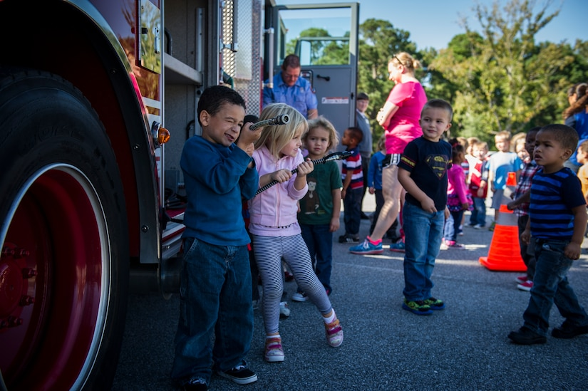 Children from the Brig. Gen. Thomas R. Mikolajcik Child Development Center pretend to put out a fire Oct. 6, 2014, at the CDC parking lot on Joint Base Charleston, S.C. This week was fire prevention week and the JBCHS Fire Department hosted several events throughout the Air Base and Weapons Station. Fire prevention Week was Oct. 5 through 11, and the JB Charleston Fire Department hosted several events around the Air Base and Weapons Station. Fire prevention week was established in 1925 by President Calvin Coolidge when he became aware that close to 15,000 American citizens had been killed in fires the previous year. (U.S. Air Force photo/Airman 1st Class Clayton Cupit)