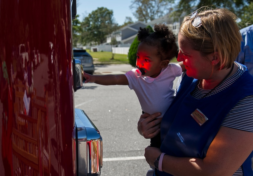 A child from the Brig. Gen. Thomas R. Mikolajcik Child Development Center reaches for a light on a Joint Base Charleston Fire Department fire truck with assistance from a CDC staff member Oct. 6, 2014, at the CDC parking lot on Joint Base Charleston, S.C. Fire prevention Week was Oct. 5 through 11, and the JB Charleston Fire Department hosted several events around the Air Base and Weapons Station. Fire prevention week was established in 1925 by President Calvin Coolidge when he became aware that close to 15,000 American citizens had been killed in fires the previous year. (U.S. Air Force photo/Airman 1st Class Clayton Cupit)