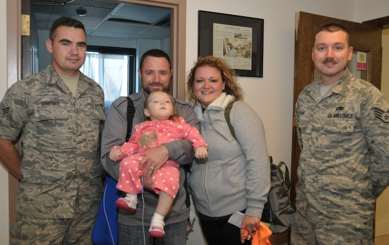 Senior Airman James Comstock (left) and Staff Sgt. Jason Stark (right) presented a check of $500 on behalf of the 109th Airlift Wing's First Six Council to the LeClaire family, Gene, Dena and 22-month-old Sophia. Sophia has cerebral palsy, and the council raised money  during the wing's recent Family Day to help with her medical expenses. (U.S. Air National Guard photo by Tech. Sgt. Catharine Schmidt/Released)