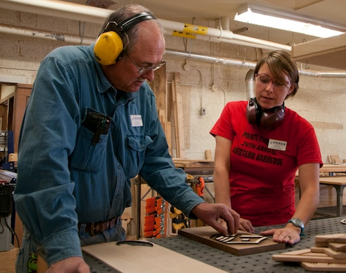 Paul Gregg, 90th Force Support Squadron wood crafter, and Sarah Dyer, 90th FSS recreational assistant, discuss a woodworking project they are working on Oct. 8, 2014. Gregg, Dyer and Dave Holmquist, 90th FSS wood crafter, form the wood shop team at the F.E. Warren Arts and Crafts Center. (U.S. Air Force photo by Senior Airman Jason Wiese)