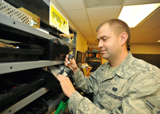 Airman 1st Class Adam Saulsbury, 319th Communications Squadron client system technician, retrieves a dongle cord in order to connect two computer monitors, on Oct. 8, 2014, at the 319th CS CSTR shop on Grand Forks Air Force Base, N.D. Saulsbury was selected as the base's Warrior of the Week for the second week in October 2014. (U.S. Air Force photo/Senior Airman Xavier Navarro)