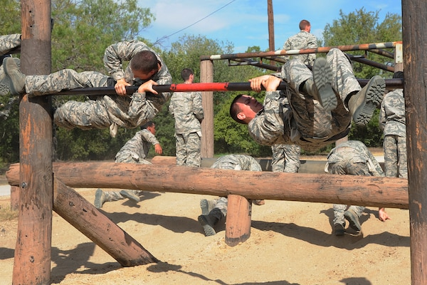 Basic military trainees swing around a bar as part of the basic military training obstacle course at Sept. 24, 2014J Joint Base San Antonio-Lackland. The obstacle course was about a mile to a mile and a half long depending on what 14 obstacles were open. The two water obstacles were closed seasonally. The course was permanently closed the same day and new one was integrated into the Creating Leaders, Airmen, and Warriors, or CLAW program and became fully operational Sept. 29. (U.S. Air Force photo by Senior Airman Krystal Jeffers/Released)
