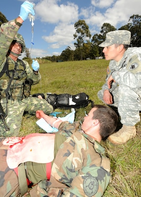 Staff Sgt. Robert Hogeland (right), U.S. Army South's medical directorate clinical operations noncommissioned officer in charge, watches as Uruguayan Marine Primero Oscar Trindade administers an IV during a tactical combat lifesaver course subject matter expert exchange Sept. 18 in Toledo, Uruguay.   Photo by Robert R. Ramon