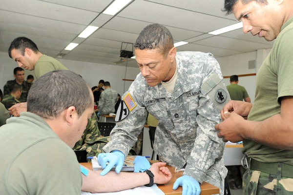 Master Sgt. Dean Dawson (center), a medical operations noncommissioned officer in charge with U.S. Army South's medical directorate, demonstrates how to administer an IV during a tactical combat lifesaver course subject matter expert exchange Sept. 17 in Toledo, Uruguay.   Photo by Robert R. Ramon