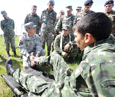 Uruguayan soldiers demonstrate how to splint a fracture on U.S. Navy Senior Chief Petty Officer Fernando Gonzalez, assigned to the Navy Medicine Training Support Center based at Joint Base San Antonio-Fort Sam Houston, during a tactical combat lifesaver course subject matter expert exchange Sept. 16 in Toledo, Uruguay.  Photo by Robert R. Ramon