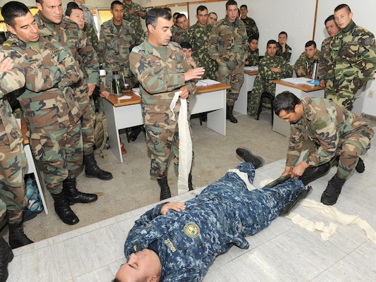 Uruguayan soldiers demonstrate how to splint a fracture on U.S. Navy Senior Chief Petty Officer Fernando Gonzalez, assigned to the Navy Medicine Training Support Center based at Joint Base San Antonio-Fort Sam Houston, during a tactical combat lifesaver course subject matter expert exchange Sept. 16 in Toledo, Uruguay.