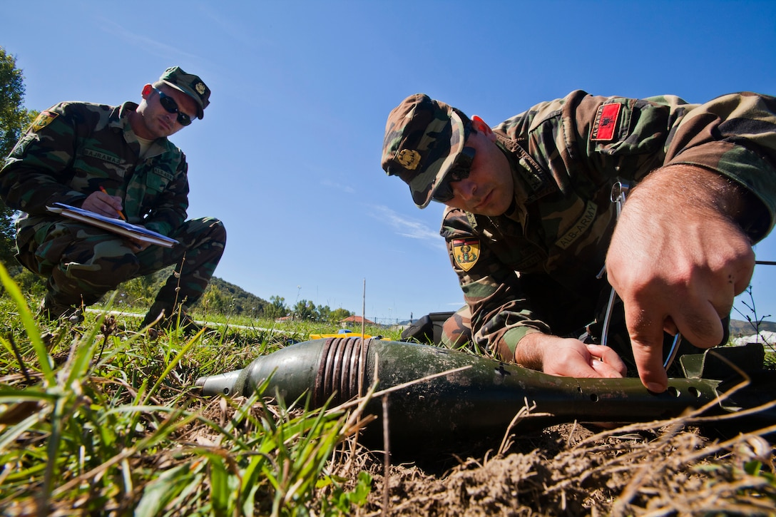 Albanian Army Lance Cpl. Ervin Bajramaj, left, observes 1st Lt. Arlind Nushi's progress during a practical problem – an EOD process that uses munition replicas to test future EOD technicians at Peze Helmes, Republic of Albania, Sept. 24, 2014. In September 2014, members of the 177th Fighter Wing Explosive Ordnance Disposal team, New Jersey Air National Guard, trained Albanian Army EOD soldiers to become level 1 EOD trainers. New Jersey National Guard Airmen and Soldiers have been training their Albanian counterparts for more than 20 years as part of the State Partnership Program between the state of New Jersey and the Republic of Albania. (U.S. Air National Guard photo by Master Sgt. Mark C. Olsen /Released)