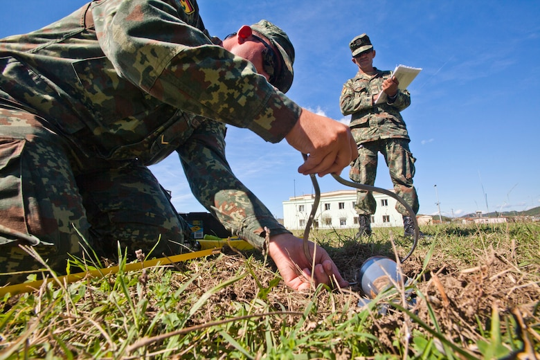 Albanian Army Cpl. Hajredin Istrefi, right, observes as Lance Cpl. Dorjan Isufi, measures an unexploded munition during a practical problem – an EOD process that uses munition replicas to test future EOD technicians at Peze Helmes, Republic of Albania, Sept. 23, 2014. In September 2014, members of the 177th Fighter Wing Explosive Ordnance Disposal team, New Jersey Air National Guard, trained Albanian Army EOD soldiers to become level 1 EOD trainers. New Jersey National Guard Airmen and Soldiers have been training their Albanian counterparts for more than 20 years as part of the State Partnership Program between the state of New Jersey and the Republic of Albania. (U.S. Air National Guard photo by Master Sgt. Mark C. Olsen /Released)