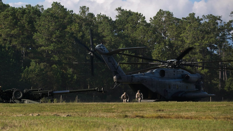 Marines disembark a CH-53E Super Stallion to prepare a M777 Howitzer for firing during a reactionary combat training exercise aboard Marine Corps Base Camp Lejeune, N.C., Sept. 30, 2014. The combined air-ground team used the training to build cohesion and improve their ability to rapidly deploy the weapon system in a combat environment. (U.S. Marine Corps photo by Lance Cpl. Olivia C. McDonald/Released)
